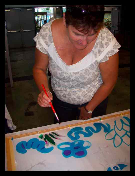 A lady learning how to paint on silk